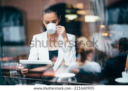 Young businesswoman drinking coffee and using tablet computer in cafe - stock photo