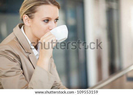 young businesswoman drinking coffee during break - stock photo