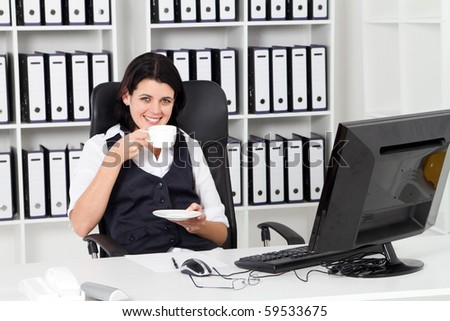 young businesswoman drinking coffee in office - stock photo