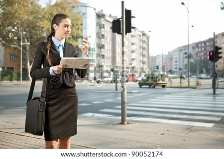 young businesswoman drinking coffee on street - stock photo