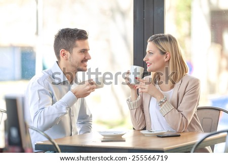 Young businesswoman drinking tea and young businessman drinking coffee in a coffee shop. - stock photo