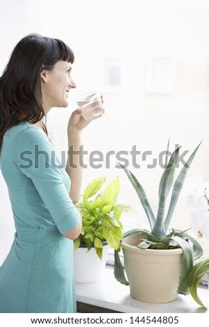 Young businesswoman drinking water by plants - stock photo