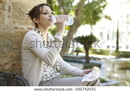 Young businesswoman drinking water from a small plastic bottle while having a lunch break in the park. - stock photo