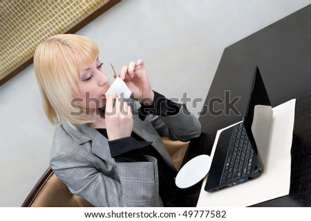 young businesswoman drinks coffee at table with netbook - stock photo
