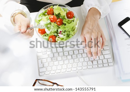 Young businesswoman eating a salad while working in office. /Young businesswoman typing on the laptop. - stock photo