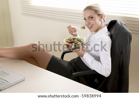 Young businesswoman eating salad in her office - stock photo