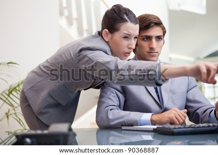 Young businesswoman explaining computer program to colleague - stock photo