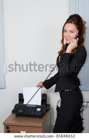 young businesswoman faxing document - stock photo
