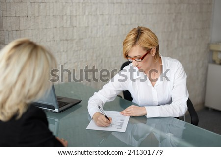 Young businesswoman fill out the form in office - stock photo