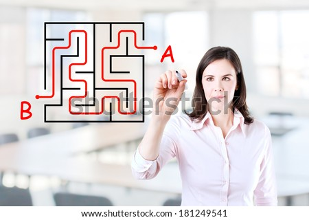 Young businesswoman finding the maze solution writing on the whiteboard. Office background.