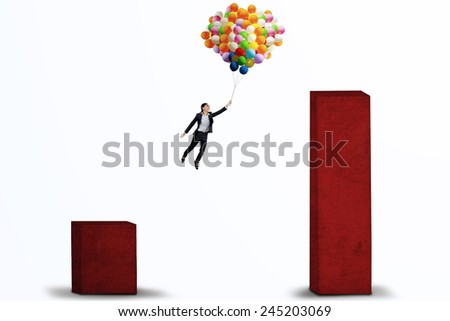 Young businesswoman flying with balloons over upward business chart to higher chart - stock photo