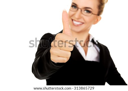 Young businesswoman gesturing thumbs up. - stock photo