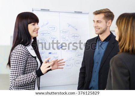 Young businesswoman giving a presentation or holding a meeting with her successful team as she stands in front of a flip chart explaining something - stock photo