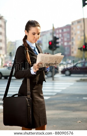 young businesswoman going to work and reading newspaper, outdoor - stock photo
