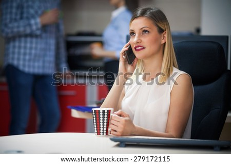 Young businesswoman having a coffee break and talking on the phone in the office - stock photo