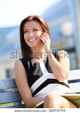 Young businesswoman having a conversation using a smartphone on a phone call while sitting on a city park bench, smiling - stock photo