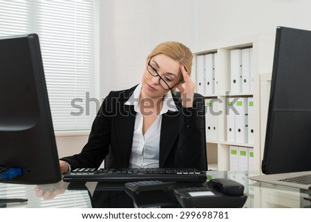 Young Businesswoman Having Headache At Desk In Office
