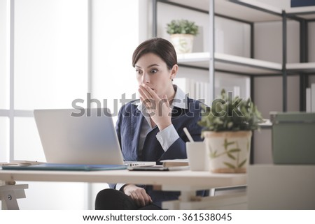 Young businesswoman having problems with her computer, she is staring shocked at the screen with an hand over mouth - stock photo