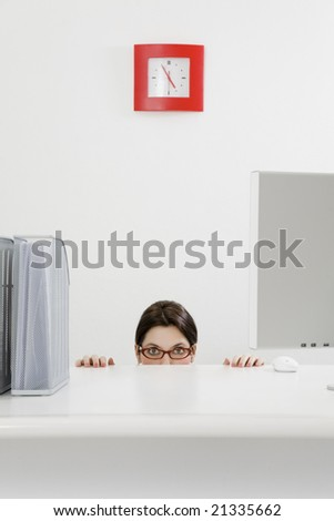 Young businesswoman hiding behind desk. Copy space