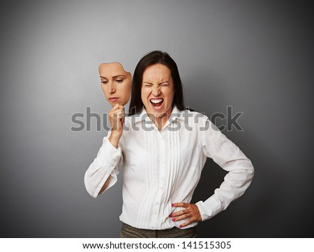 young businesswoman hiding her anger behind the mask of indifferent mood - stock photo