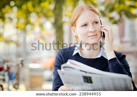 Young businesswoman hold a newspaper in her hand and calls by phone. Copy space available. - stock photo