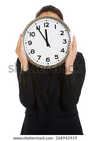 Young businesswoman holding a big clock.