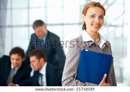 Young businesswoman holding a blue folder with her colleagues working at the background.