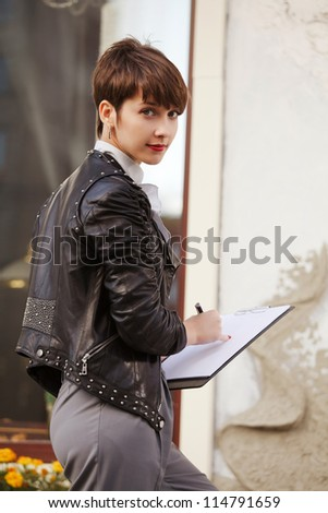 Young businesswoman holding a clipboard - stock photo