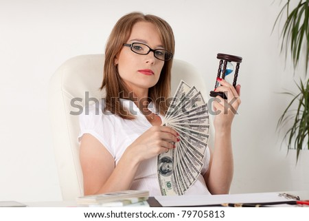 Young businesswoman holding a hourglass and money.  Concept of time is money. - stock photo