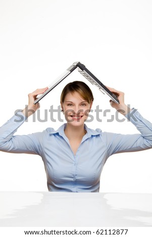young businesswoman holding a laptop above her head like a roof - stock photo