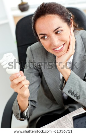 Young businesswoman holding a light bulb sitting in her office at her desk - stock photo