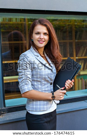 Young businesswoman holding a pen and folder with papers - stock photo