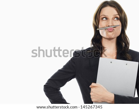 Young businesswoman holding a pen under her nose against white background - stock photo
