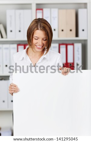 Young businesswoman holding big white board at office - copyspace for text - stock photo