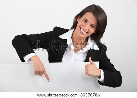 Young businesswoman holding blank message board - stock photo