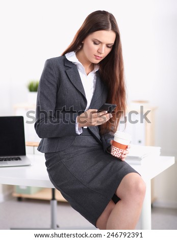 Young businesswoman holding disposable cup and smartphone