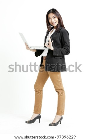Young businesswoman holding her laptop and giving ok hand sign