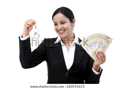 Young businesswoman holding house key and currency notes - stock photo