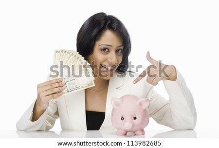 Young businesswoman holding Indian paper currency and piggy bank
