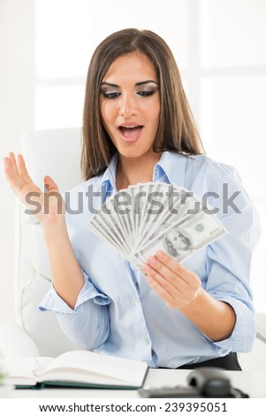 Young businesswoman holding money in hand and with an expression of surprise on her face looking into money.