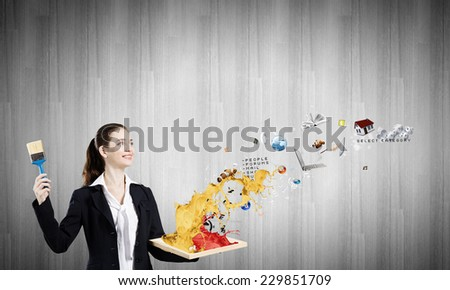 Young businesswoman holding paint brush and wooden frame - stock photo