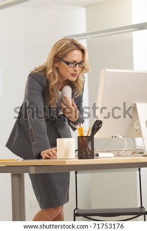 Young businesswoman holding phone while looking at computer