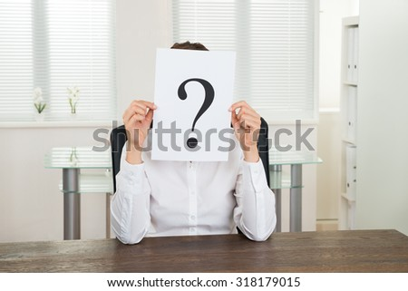 Young Businesswoman Holding Question Mark Paper In Front Of Face At Desk