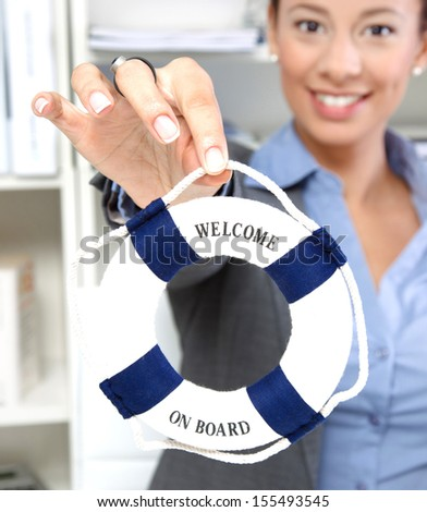 Young businesswoman holding small life buoy with the text: welcome on board. Concept for teamwork. - stock photo