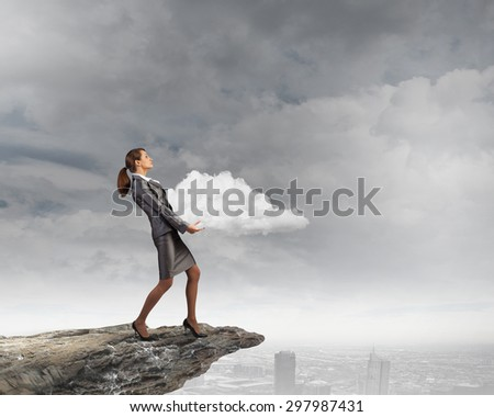 Young businesswoman holding white cloud in hands