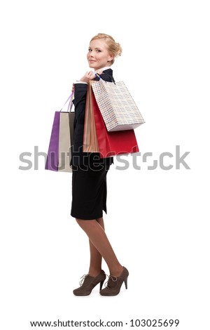 Young businesswoman in a black suit holding shopping bags, isolated on white