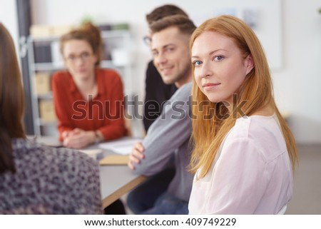 Young businesswoman in a meeting with co-workers turning in her chair to look thoughtfully at the camera with a serious expression - stock photo