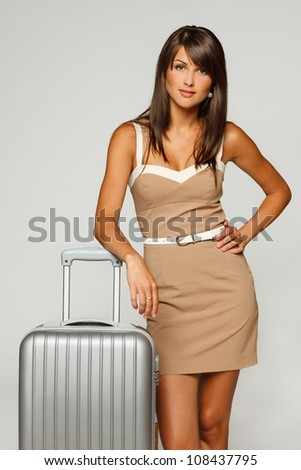 Young businesswoman in elegant beige dress going to business trip standing leaning on her silver travel suitcase, against gray background - stock photo
