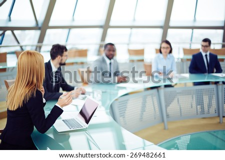Young businesswoman in formalwear sitting at conference - stock photo