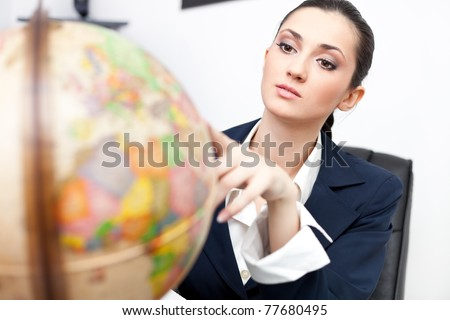 young businesswoman in office looking globe - stock photo